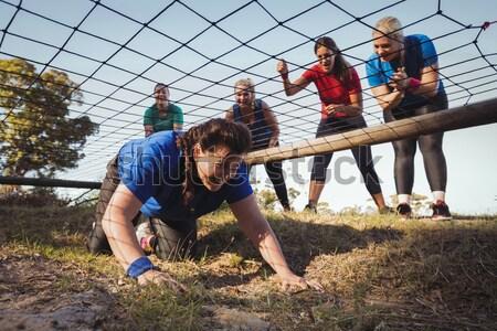 Trainer assisting girl to climb monkey bars during obstacle course training Stock photo © wavebreak_media