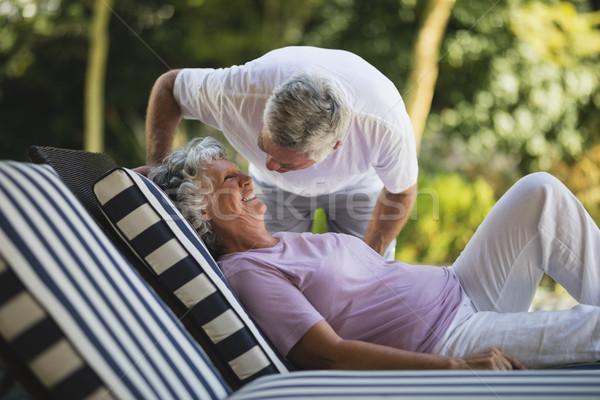 Senior man bending over woman resting on lounge chair Stock photo © wavebreak_media