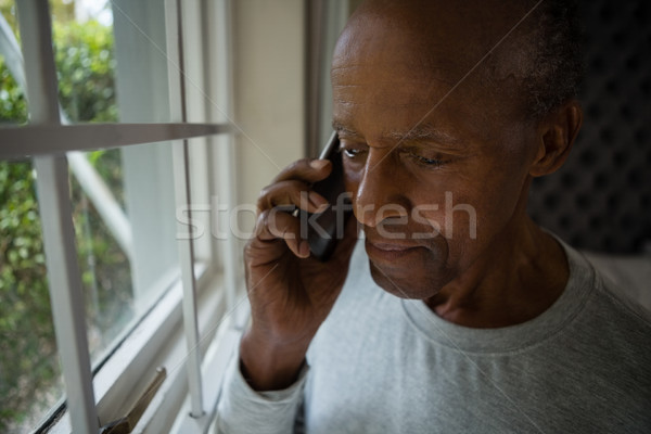 Ernstig senior man praten mobiele telefoon venster Stockfoto © wavebreak_media