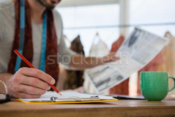 Designer drawing sketch on paper at table in office Stock photo © wavebreak_media