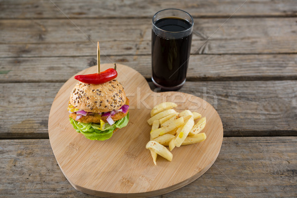 Burger with French fries on heart shape cutting board by drink Stock photo © wavebreak_media