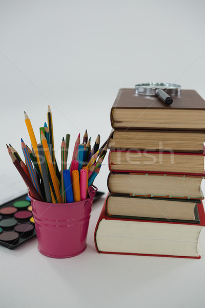 Book stack, magnifying glass, color pencils and palette on white background Stock photo © wavebreak_media