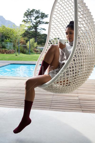 Donna tazza di caffè rilassante swing sedia Foto d'archivio © wavebreak_media