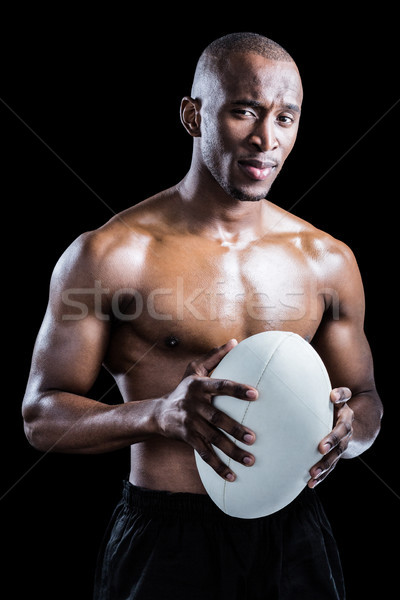 Portrait of confident shirtless athlete holding rugby ball Stock photo © wavebreak_media