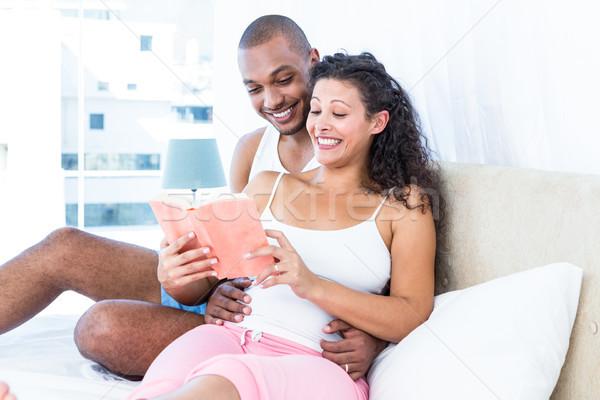 Happy husband with pregnant wife reading book Stock photo © wavebreak_media