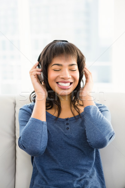 Casual smiling woman listening music with headphones Stock photo © wavebreak_media