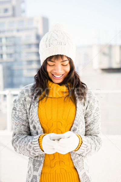 Smiling woman wearing winter clothes and typing on her phone Stock photo © wavebreak_media