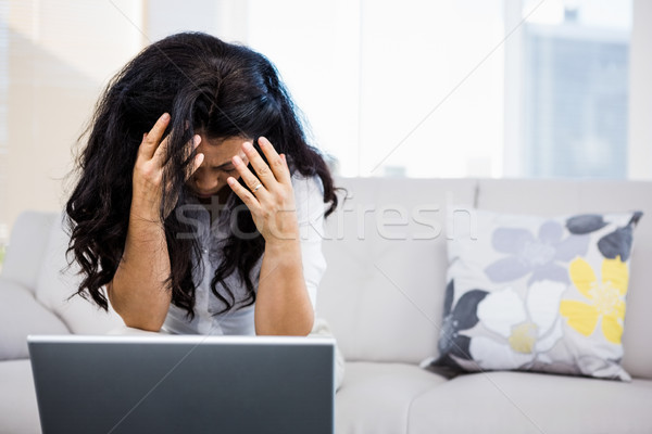 Concerned woman sitting at home Stock photo © wavebreak_media