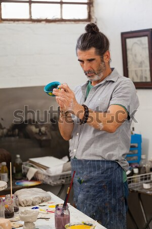 Boy painting a bowl in pottery shop Stock photo © wavebreak_media