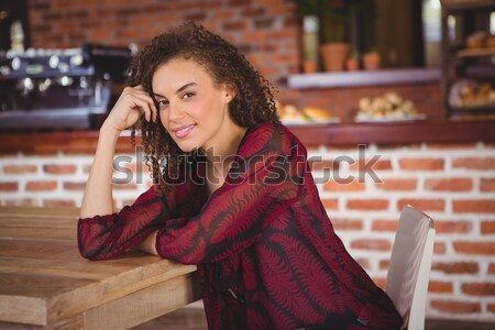 Beautiful woman sitting on chair and using mobile phone at counter Stock photo © wavebreak_media