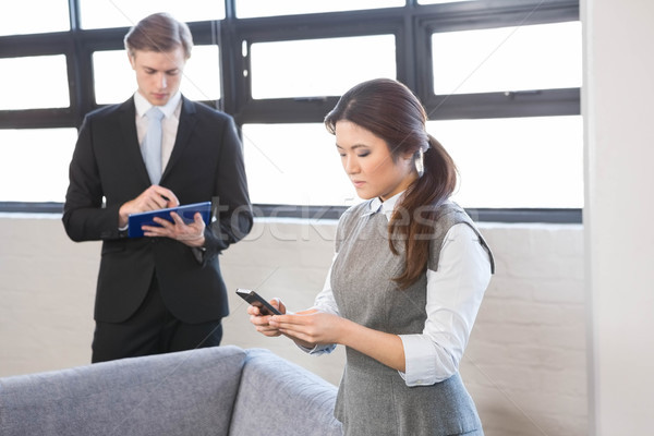 Businesswoman text messaging on smartphone and businessman using Stock photo © wavebreak_media