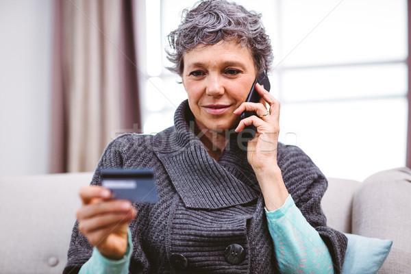 Mulher madura cartão de crédito falante telefone móvel Foto stock © wavebreak_media