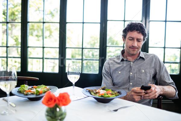 Man in a restaurant using mobile phone Stock photo © wavebreak_media