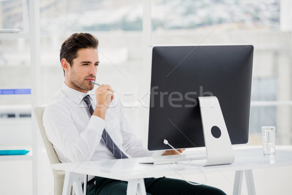 Businessman using computer and taking notes Stock photo © wavebreak_media