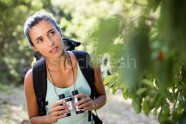Woman concentrated holding binoculars  Stock photo © wavebreak_media