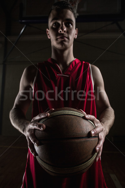 Portrait of basketball player unsmiling and holding a basketball Stock photo © wavebreak_media