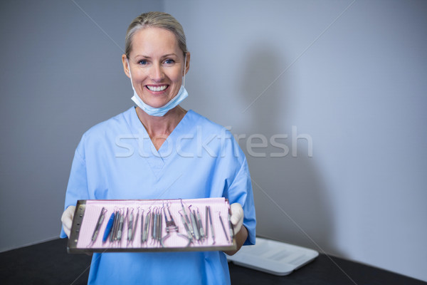 Smiling dental assistant holding tray with equipment in dental c Stock photo © wavebreak_media