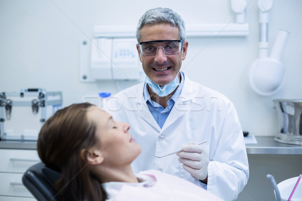 Smiling Dentist examining a patient with tools Stock photo © wavebreak_media
