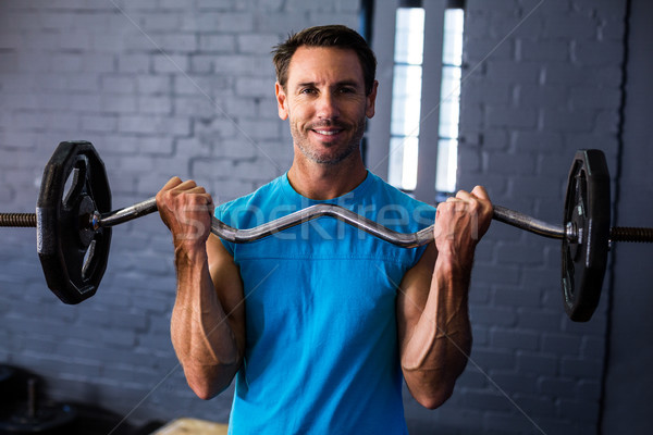 Smiling man exercising with barbell  Stock photo © wavebreak_media