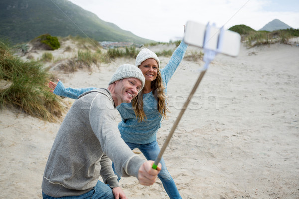 Stock photo: Happy couple taking a selfie from selfie stick