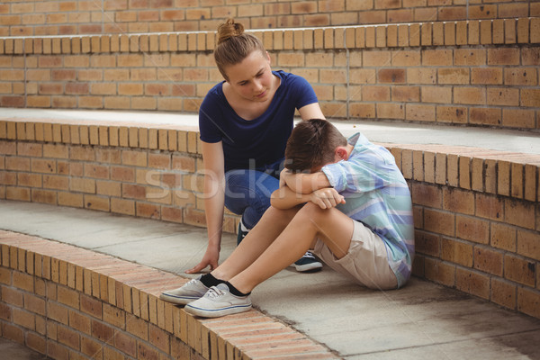 Schoolgirl consoling her sad friend on steps in campus Stock photo © wavebreak_media
