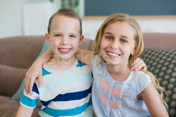 Portrait of smiling brother and sister embracing on couch in living room at home Stock photo © wavebreak_media