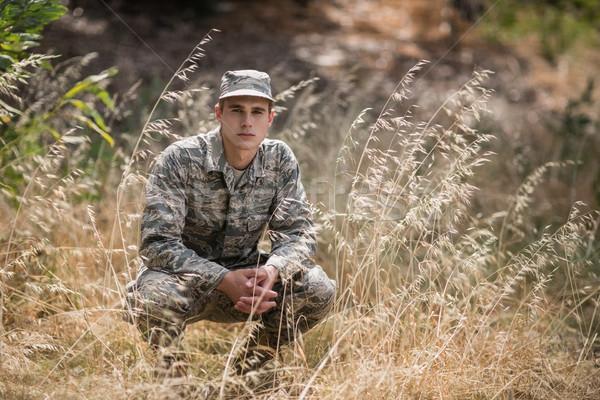 Portrait of military soldier crouching in grass Stock photo © wavebreak_media