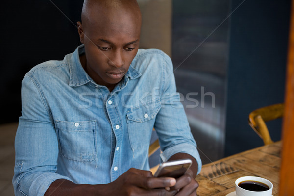 Man using mobile phone at wooden table in coffee house Stock photo © wavebreak_media