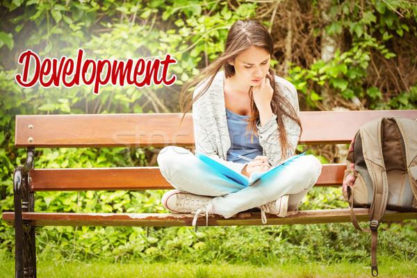 Development against smiling student sitting on bench reading boo Stock photo © wavebreak_media