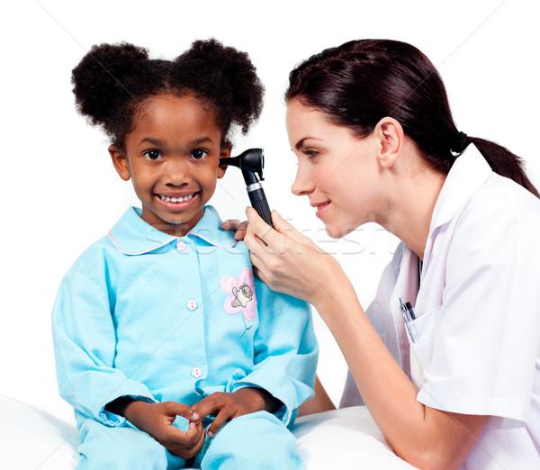 Female doctor checking her patient's ears  Stock photo © wavebreak_media