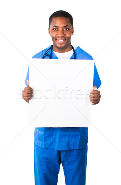 Handsome doctor wearing scrubs and showing a white card Stock photo © wavebreak_media