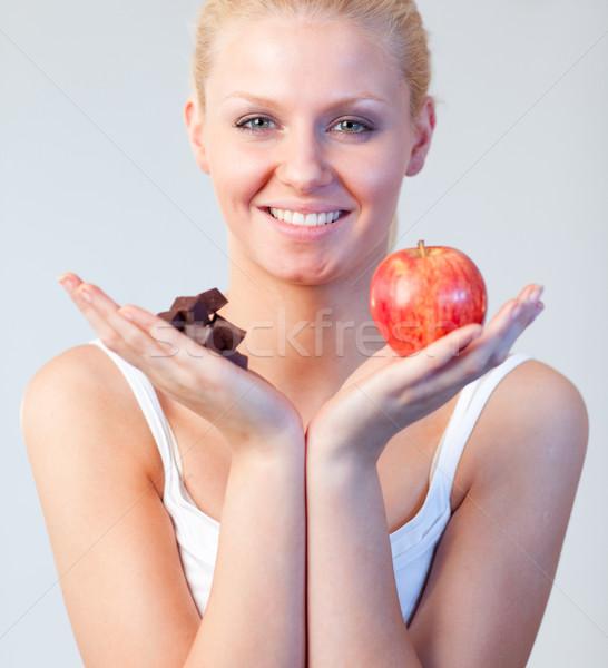 Friendly woman holding chocolate and apple focus on woman  Stock photo © wavebreak_media
