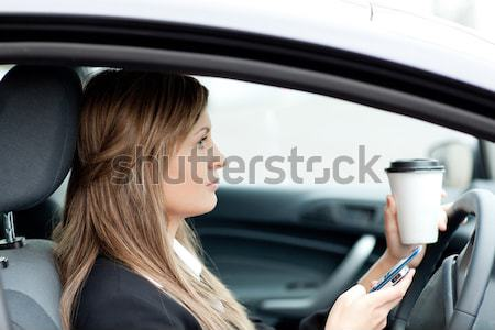 Charming businesswoman eating and holding a drinking cup while driving to work Stock photo © wavebreak_media