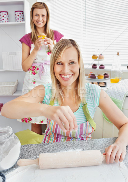 Animated female friends baking muffins in the kitchen smiling at the camera Stock photo © wavebreak_media