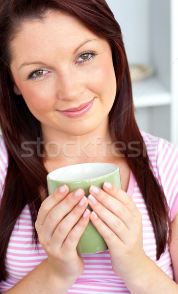 Glad woman holding a cup of coffee in the kitchen at home Stock photo © wavebreak_media