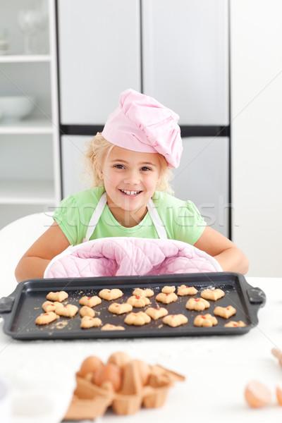 Aanbiddelijk meisje tonen cookies permanente Stockfoto © wavebreak_media