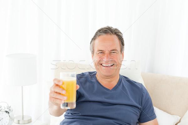 Nyugdíjas férfi néz kamera iszik dzsúz Stock fotó © wavebreak_media