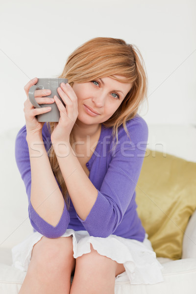 Pretty red-haired woman holding a cup of coffee and posing while sitting on a sofa in the living roo Stock photo © wavebreak_media