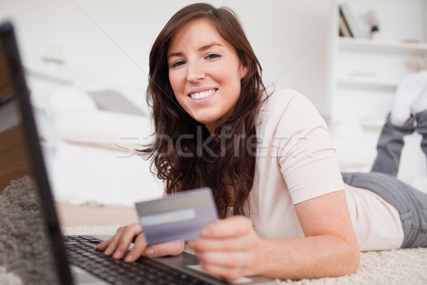 Young good looking female making a payment with a credit card on the internet while lying on a carpe Stock photo © wavebreak_media