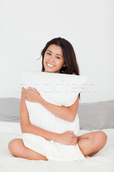 smiling woman with pillow sitting on her bed looking into camera in bedroom Stock photo © wavebreak_media