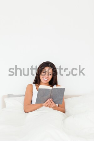 dark-haired woman reading book sitting in bed looking into camera in bedroom Stock photo © wavebreak_media