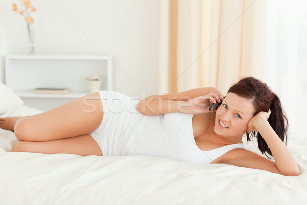 Charmant femme lit regarder caméra chambre Photo stock © wavebreak_media
