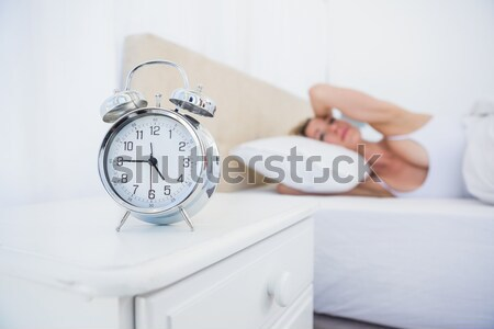 Portrait of a woman switching off her alarm clock in her bedroom Stock photo © wavebreak_media