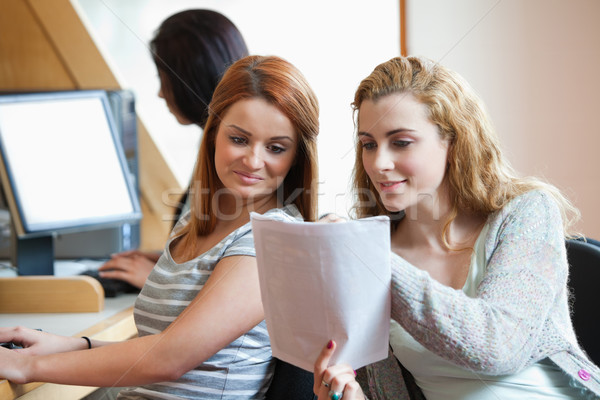 Happy student showing her notes to her classmate in an IT room Stock photo © wavebreak_media