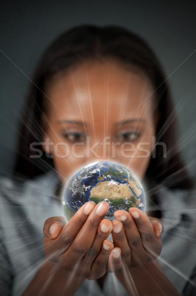 Woman holding a glowing Earth against a dark background Stock photo © wavebreak_media