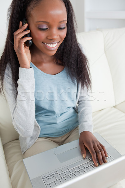 Close up of smiling woman on the phone while using notebook Stock photo © wavebreak_media