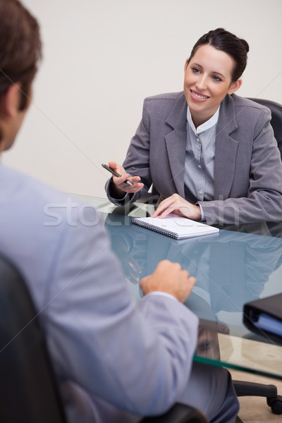 Smiling young businesswoman with notepad in negotiation Stock photo © wavebreak_media