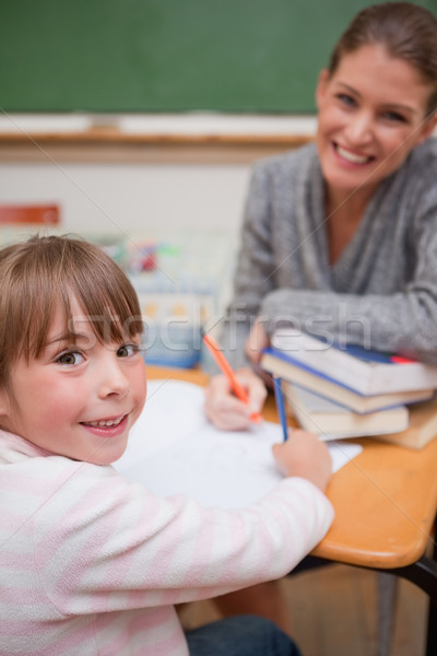Portrait of a smiling teacher explaining something to her pupil in a classroom Stock photo © wavebreak_media