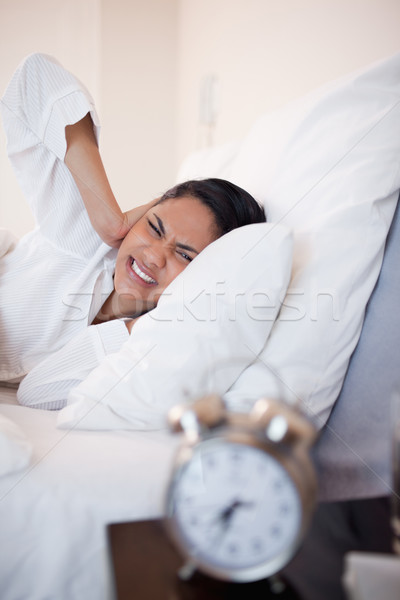 Side view of young woman getting ungently woken by alarm clock Stock photo © wavebreak_media