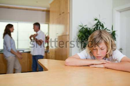 Stock photo: Boy is sad about fighting parents behind him
